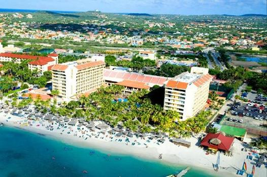 Set amid the pristine white sands of Aruba's famed Palm Beach, ...